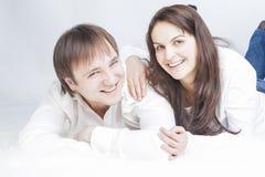 Retrato da família caucasiano nova que encontra-se no assoalho abraçado junto Imagens de Stock