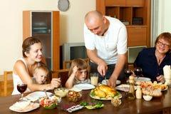 Retrato da família multigeneration feliz que come a galinha com wi Foto de Stock Royalty Free