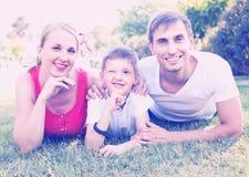 Retrato da família nova com o menino que encontra-se no parque Foto de Stock