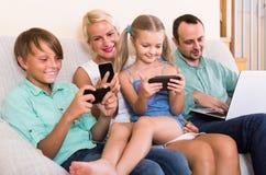 Retrato da família que joga com dispositivos em casa Fotografia de Stock