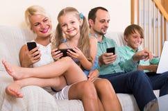 Retrato da família que joga com dispositivos em casa Fotografia de Stock Royalty Free