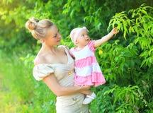 Retrato da filha nova feliz da mãe e do bebê que veste um vestido Fotografia de Stock