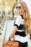 Retrato da forma da mulher loura nova de sorriso com desgaste da bolsa Fotografia de Stock Royalty Free