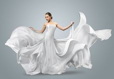 Retrato da forma de uma mulher bonita em um vestido branco de ondulação A tela clara voa no vento foto de stock royalty free
