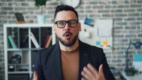 Retrato da gritaria farpada irritada e de apontar do indivíduo na câmera no escritório video estoque