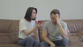 Retrato da gritaria irritada da mulher em seu telefone celular triste da exibição do marido com mensagens de seu paramour em casa filme