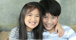 Retrato da irmã feliz e do irmão asiáticos da família que actuam na cara uma câmera de vista video estoque