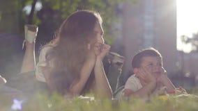 Retrato da irmã mais idosa e do irmão mais novo fora O menino e a menina que encontram-se na grama junto no parque ver?o video estoque