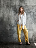 Retrato da jovem mulher à moda na camisa branca e na calças amarela imagens de stock royalty free
