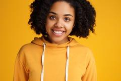 Retrato da jovem mulher afro-americano atrativa com sorriso bonito vestida na roupa ocasional sobre o amarelo imagem de stock royalty free