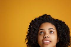 Retrato da jovem mulher afro-americano atrativa com sorriso bonito vestida na roupa ocasional sobre o amarelo fotos de stock