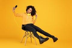 Retrato da jovem mulher afro-americano engraçada com sorriso bonito vestida na roupa ocasional e nos fones de ouvido que sentam-s imagens de stock royalty free