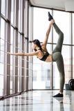 Retrato da jovem mulher apta muscular na ioga praticando do sportswear à moda no grande salão do gym, estando na pose da vaca que fotografia de stock