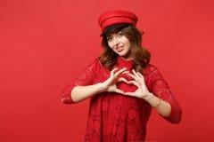 Retrato da jovem mulher atrativa no vestido do laço, tampão que mostra o coração da forma com as mãos isoladas na parede vermelha fotografia de stock royalty free