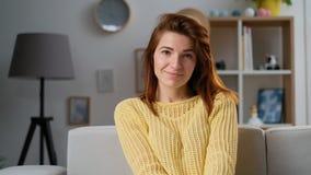 Retrato da jovem mulher atrativa que olha na câmera na sala de visitas em casa Cabeça de gerencio da menina bonita à câmera vídeos de arquivo