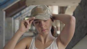 Retrato da jovem mulher atrativa que põe sobre o tampão militar em sua cabeça e que olha na posição da câmera no abandonado video estoque