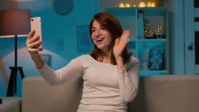 Retrato da jovem mulher atrativa que senta-se no sofá na noite e que tem uma chamada video de Skype com amigos em linha filme