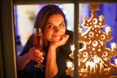 Retrato da jovem mulher através da janela que comemora o Ev de ano novo Fotografia de Stock Royalty Free