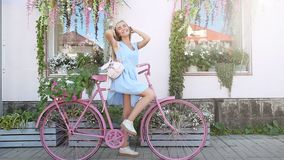 Retrato da jovem mulher da beleza com trouxa e a bicicleta cor-de-rosa Estilo de vida do conceito Floresce a decoração filme