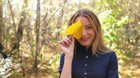Retrato da jovem mulher bonita brincalh?o com a folha amarela do outono na floresta em cores da queda movimento 4k lento filme