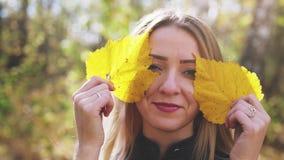 Retrato da jovem mulher bonita brincalh?o com a folha amarela na floresta do outono 3840x2160 Movimento lento vídeos de arquivo