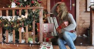 Retrato da jovem mulher bonita com as caixas de presente de exame do cabelo longo em um patamar da casa filme