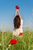 Retrato da jovem mulher bonita com as papoilas no campo com um ramalhete das papoilas Moça em um campo da papoila, vista traseira Imagens de Stock