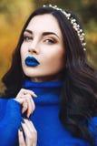 Retrato da jovem mulher bonita com bordos azuis e a camiseta azul com o acessório em sua cabeça no parque Fotos de Stock