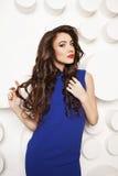 Retrato da jovem mulher bonita com cabelo marrom longo encaracolado no vestido azul Foto de Stock Royalty Free