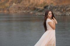 Retrato da jovem mulher bonita com a flor marrom longa do rosa do cabelo que levanta no estúdio sobre o fundo escuro Foto de Stock Royalty Free