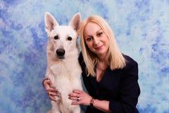 Retrato da jovem mulher bonita com o cão no fundo azul Imagens de Stock