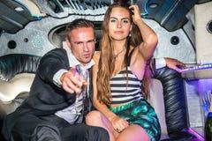 Retrato da jovem mulher bonita com o homem que guarda a gripe do champanhe Fotografia de Stock