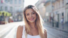 Retrato da jovem mulher bonita com com olhos azuis e sorriso atrativo Está no meio da rua da vídeos de arquivo
