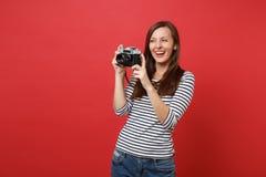 Retrato da jovem mulher bonita de sorriso em roupa listrada que mantém a câmera retro da foto do vintage isolada na parede vermel imagem de stock
