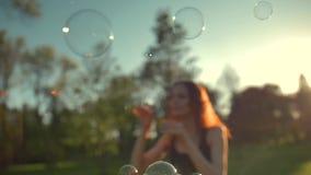 Retrato da jovem mulher bonita do gengibre Bolhas de sopro no parque vídeos de arquivo