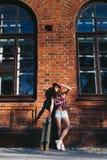 Retrato da jovem mulher bonita elegante com um skate Fotos de Stock Royalty Free