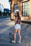 Retrato da jovem mulher bonita elegante com um skate Imagem de Stock Royalty Free