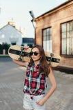 Retrato da jovem mulher bonita elegante com um skateboar Fotos de Stock