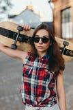 Retrato da jovem mulher bonita elegante com um skateboar Imagens de Stock