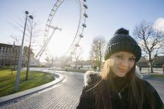 Retrato da jovem mulher bonita na frente do olho de Londres, Londres, Reino Unido Imagem de Stock Royalty Free