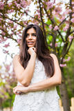 Retrato da jovem mulher bonita que aprecia o dia ensolarado no parque durante a estação da flor de cerejeira em um dia de mola ag fotografia de stock royalty free