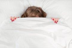 Retrato da jovem mulher bonita que encontra-se na cama sob a cobertura Fotos de Stock