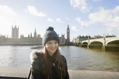 Retrato da jovem mulher bonita que está pelo rio Tamisa, Londres, Reino Unido Imagem de Stock Royalty Free