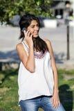 Retrato da jovem mulher bonita que fala no telefone exterior Fotografia de Stock