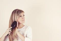 Retrato da jovem mulher bonita que penteia seus cabelo e sorriso foto de stock royalty free