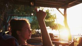 Retrato da jovem mulher bonita que senta-se na espreguiçadeira e que olha o por do sol vídeos de arquivo