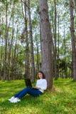 Retrato da jovem mulher bonita que senta-se na grama verde no dia de ver?o do parque ao usar o port?til imagens de stock
