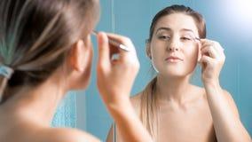 Retrato da jovem mulher bonita que usa a pinça no espelho fotografia de stock royalty free