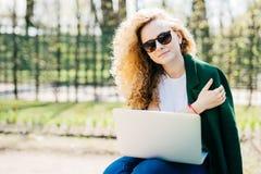 Retrato da jovem mulher bonito com os óculos de sol vestindo encaracolado do cabelo louro, o t-shirt branco e o revestimento verd fotografia de stock