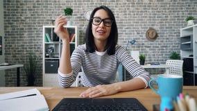 Retrato da jovem mulher bonito que skyping na mão de ondulação de fala do escritório que envia o beijo